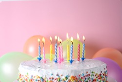 Birthday cake with burning candles and balloons on color background. Space for text