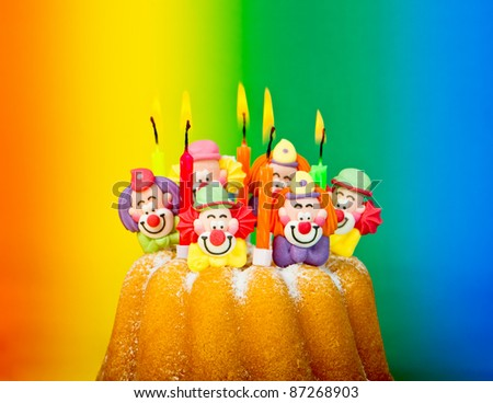 birthday cake with burning candles and decoration on colorful background