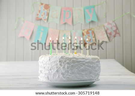 Birthday cake with candles on planks wall background