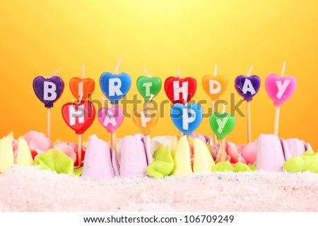 Birthday cake with candles on yellow background