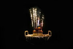Birthday cake with fireworks on table in black background