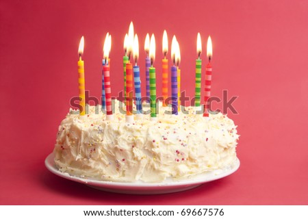 birthday cake with lots of candles on a red background
