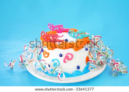 Birthday cake with the words Happy Birthday on top and decorated all around the cake with curly ribbons that say Happy Birthday. Room for text on the background.