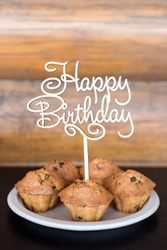 Birthday cakes and muffins with wooden greeting sign on rustic background. Wooden sing with letters Happy Birthday and holiday sweets.