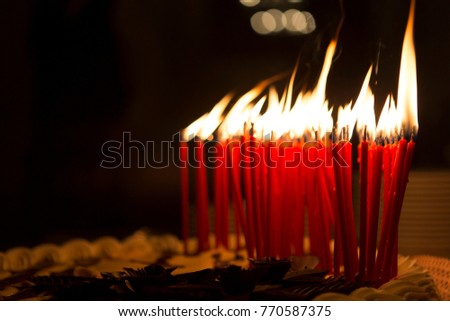 Birthday candles lit in a dark room, on top of a cake. - Shutterstock ID 770587375