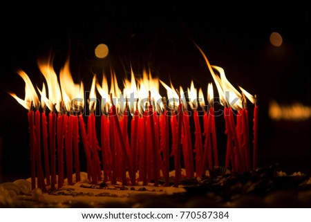 Birthday candles lit in a dark room, on top of a cake. - Shutterstock ID 770587384