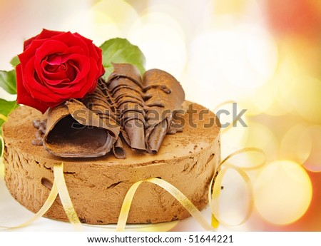 Birthday card with toffee cake and red rose over defocused lights.