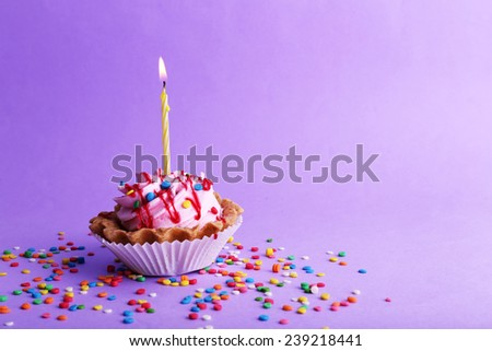 Birthday Cup Cake With Candle And Colorful Sparkles On Purple Background 239218441