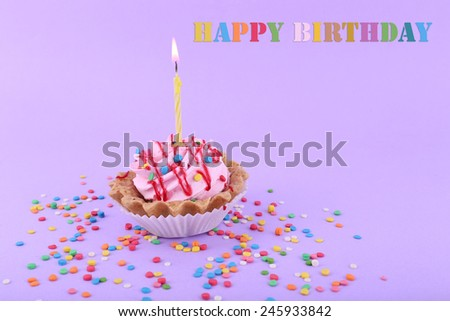 Birthday Cup Cake With Candle And Colorful Sparkles On Purple Background 245933842