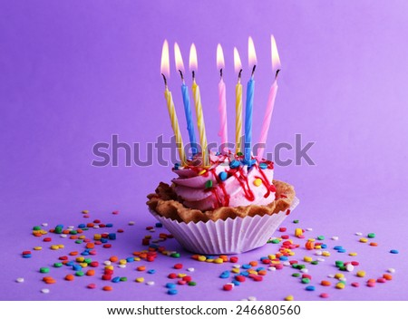 Birthday Cup Cake With Candles And Colorful Sparkles On Purple Background 246680560
