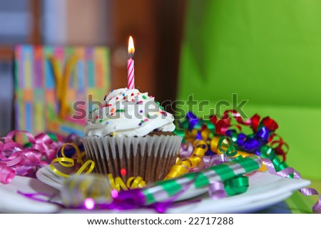 Birthday Cup Cake With One Lit Candle and Gifts in the Background