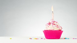 Birthday cupcake. Tasty cupcakes with white cream icing and colored sprinkles. Burning candle in a cake. Sweet delicious dessert on white wooden table. White Background with Copy space.