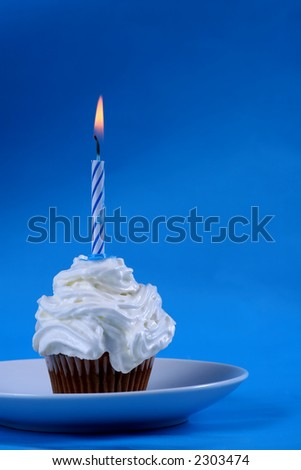 Birthday cupcake with a single candle on it on blue background