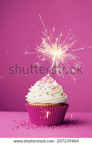 Birthday cupcake with a sparkler against a pink background