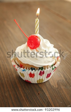 Birthday cupcake with candle and cherry on top