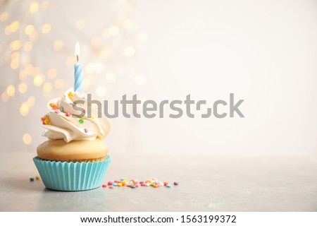 Birthday cupcake with candle on light grey table against blurred lights. Space for text
