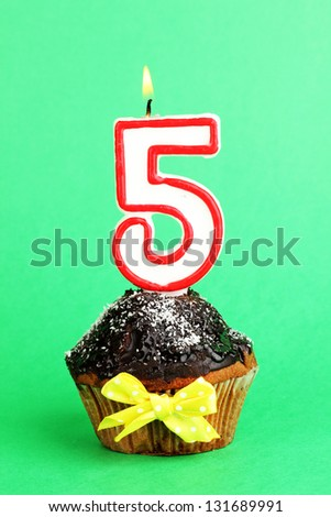Birthday cupcake with chocolate frosting on green background