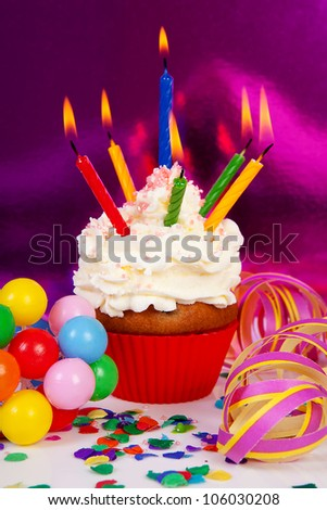 Birthday cupcake with lots of candles, party streamers and colorful confetti over purple background