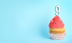 Birthday cupcake with number nine candle on blue background, space for text