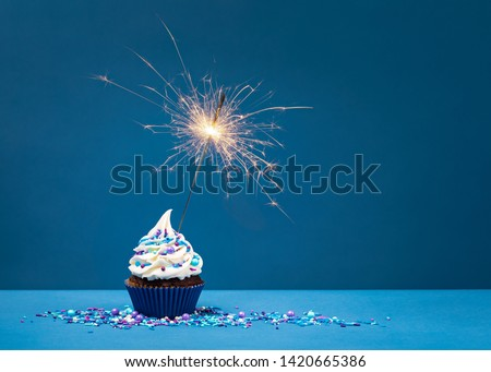 Birthday Cupcake with sparkler against a blue background. Foto stock ©