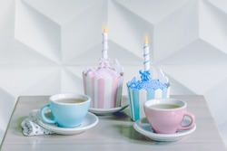 Birthday cupcakes with birthday candle and cup of tea.
