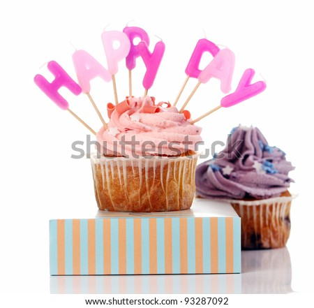 Birthday cupcakes with colorul latters on white background