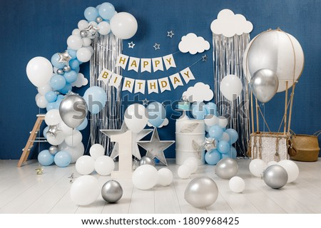 Birthday decorations - gifts, toys, balloons, garland and figure for little baby party on a blue wall background.