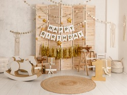 Birthday decorations with balloons, gifts, toys, garlands and candy for yearling, little baby party, celebration on a white wall background. Golden decor elements.