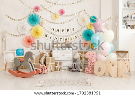 Birthday decorations with balloons, gifts, toys, garlands and candy for yearling, little baby party, selebration on a white wall background. Decor elements in unicorn colors.