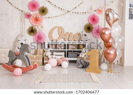 Birthday decorations with balloons, gifts, toys, garlands and candy for yearling, little baby party, celebration on a white wall background. Pink and gold Decor elements.
