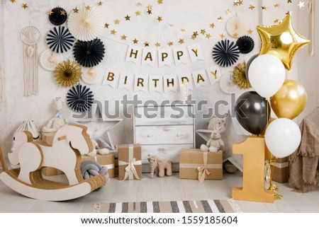 Birthday decorations with gifts, toys, balloons, garland and figure 1 for little baby party on a white wall background.