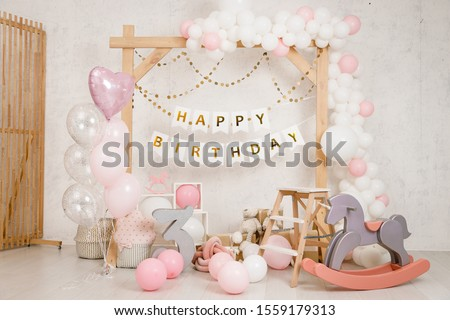 Birthday decorations with wooden arch, gifts, toys, balloons, garland and figure 3 for little baby party on a white wall background.