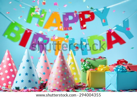 Birthday gift boxes with paper confetti on blue background