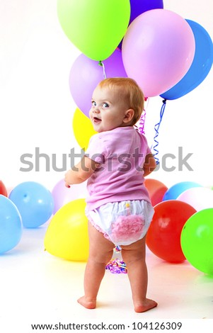 Birthday girl:  adorable baby wearing cupcake bloomer and holding balloons peeks over her shoulder