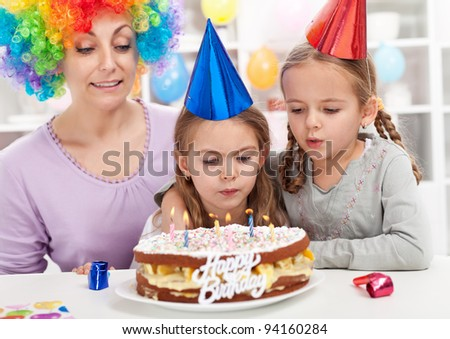 Birthday girl making a wish and blowing out candles on a cake