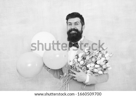 Birthday greetings. Flowers delivery. For someone special. Man bearded gentleman suit bow tie hold air balloons and bouquet. Gentleman making romantic surprise for her. Gentleman romantic date.