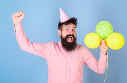 Birthday guy with happy face and big smile on blue background. Bearded man wearing paper cap having fun. Hipster with stylish beard and mustache celebrating birthday. Party perfomer at kids event.
