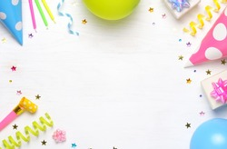 Birthday or party greeting card with copy space. Holiday frame or background with colorful balloon, gift, confetti, star, carnival cap and streamer. Top view.