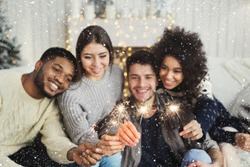Birthday or winter holidays celebration, greeting card mockup. Happy multiethnic friends holding bengal lights, copy space
