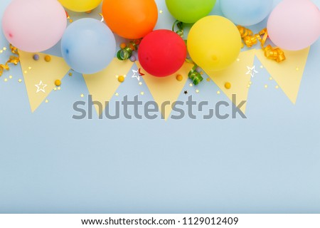 Birthday party background border with baloons and confetti, on blue surface with copy space