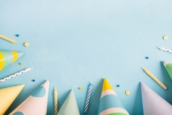 Birthday party background. Carnival caps, confetti and candles on pastel blue surface. Top view, flat lay, copy space