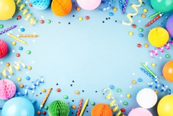 Birthday party background on blue. Top view. Frame made of colorful serpentine, balloons, candles, candies and confetti.