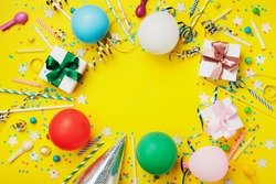 Birthday party background or frame with colorful balloon, gift, confetti, silver star, carnival cap, candy and streamer. Flat lay. Holiday flyer with copy space.
