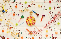 Birthday party background. Top view on holiday decorations, confetti, candles and candies bowl on white wooden planks. Celebration concept