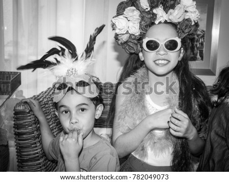 Birthday party: black and white image of a young boy wearing a mask and a young girl wearing a flower crown and sunglasses