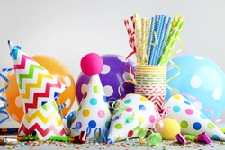 Birthday party caps, blowers and balloons on grey background