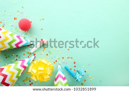 Birthday party caps, blowers and confetti on mint background