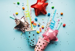 Birthday party caps,  paper straws, candy and baloons on blue background