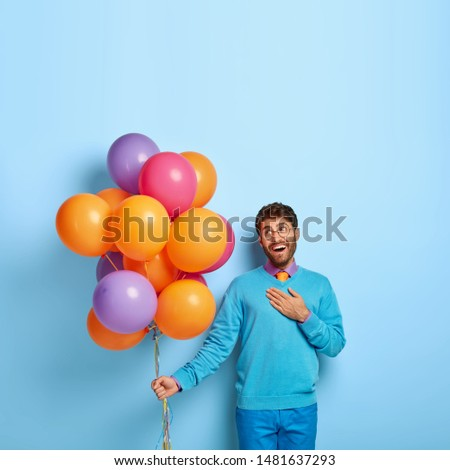 Birthday party celebration. Touched pleased guy keeps palm on chest, looks with smile at colorful balloons, impressed by words of congratulation, celebrates his 30s anniversary, enjoys holiday #1481637293