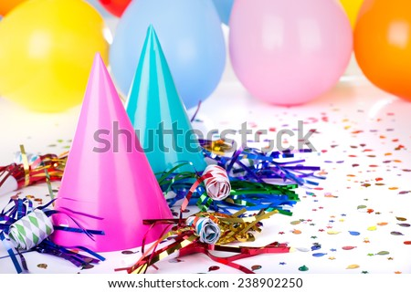 Birthday party decorations of hats, noisemakers, confetti and balloons